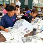 新聞を手に取り、気になる記事を探す渡慶次小学校の教師たち=読谷村瀬名波・同小