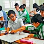 拡大したコラムに色を付けながら記事の構成を分析する2年生=21日、那覇市古島・興南中学校